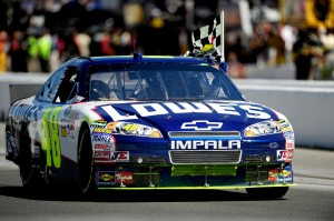 2010_Infineon_NSCS_Jimmie_Johnson_drives_with_checkered_flag